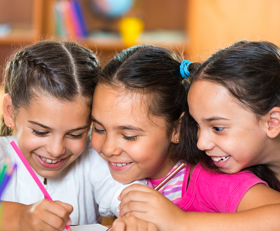 Three young Latino girls smiling and writing